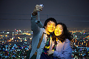 Seoul/South Korea, Republic of Korea, KOR, 30.04.2009: Young couple photographing each other during an evening mood at the lowest observation deck of the N Seoul Tower surrounded by lockers. N Seoul Tower is a communication tower located in Seoul, South Korea. Built in 1969, and opened to the public in 1980, the tower measures 236.7 m (777 ft) in height (from the base) and tops out at 479.7 m (1,574 ft) above sea level.<br /> <br /> Seoul/Suedkorea, Republik Korea, KOR, 30.04.2009: Junges Paar fotografiert sich in abendlicher Stimmung auf der unteren Aussichtsplattform des N Seoul Towers in der koreanischen Haupstadt umringt mit Wuenschen versehenen Schloessern. Der N Seoul Tower ist ein der Oeffentlichkeit zugaenglicher Fernsehturm in der suedkoreanischen Hauptstadt Seoul. Der 236,7 Meter hohe Turm steht auf 243 m ue. N.N. des Berges Namsan.