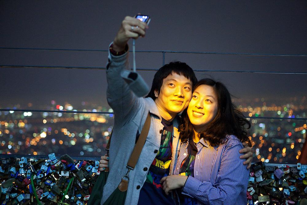 Seoul/South Korea, Republic of Korea, KOR, 30.04.2009: Young couple photographing each other during an evening mood at the lowest observation deck of the N Seoul Tower surrounded by lockers. N Seoul Tower is a communication tower located in Seoul, South Korea. Built in 1969, and opened to the public in 1980, the tower measures 236.7 m (777 ft) in height (from the base) and tops out at 479.7 m (1,574 ft) above sea level.<br /> <br /> Seoul/Suedkorea, Republik Korea, KOR, 30.04.2009: Junges Paar fotografiert sich in abendlicher Stimmung auf der unteren Aussichtsplattform des N Seoul Towers in der koreanischen Haupstadt umringt mit Wuenschen versehenen Schloessern. Der N Seoul Tower ist ein der Oeffentlichkeit zugaenglicher Fernsehturm in der suedkoreanischen Hauptstadt Seoul. Der 236,7 Meter hohe Turm steht auf 243 m ue. N.N. des Berges Namsan.