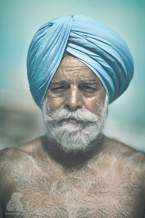 After completing his bathing ritual, a man wearing a turquoise 'dastar' poses for a portrait. In the west, the Sikh dastar is often mistaken for an afghan, yemeni, or iranian headdress. The distinctive Sikh turban is a symbol of dedication, sovereignty, piety and is a mandatory article of faith for those who have been baptised.