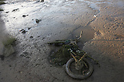Abandoned trail bike covered in river weed and mud is exposed by low-tide Thames waters at Greenhithe, Kent