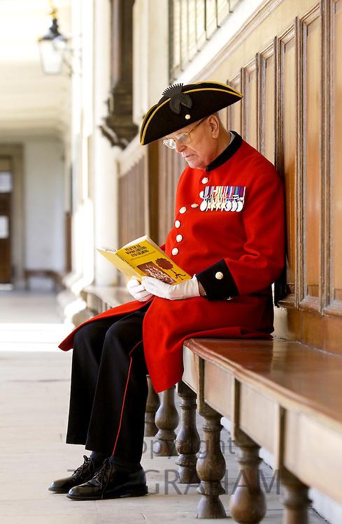 Chelsea Pensioner war veteran reading at the Royal Hospital in Chelsea, London