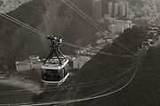 B & W photo of a cablecar on the way to the top of Sugarloaf Mountain looking back toward Botafogo Bay