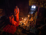 "14 MARCH 2105 - SIEM REAP, SIEM REAP, CAMBODIA: Buddhist monks pray in a prayer room in Bayon, one of the temples in Angkor Thom, a part of the Angkor Wat complex. Bayon was built in 12th or 13th century CE. The area known as ""Angkor Wat"" is a sprawling collection of archeological ruins and temples. The area was developed by ancient Khmer (Cambodian) Kings starting as early as 1150 CE and renovated and expanded around 1180CE by Jayavarman VII. Angkor Wat is now considered the seventh wonder of the world and is Cambodia's most important tourist attraction.   PHOTO BY JACK KURTZ"