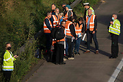 Surrey Police officers monitor Insulate Britain climate activists on the hard shoulder alongside the clockwise carriageway of the M25 between Junctions 9 and 10 on 21st September 2021 in Ockham, United Kingdom. The activists walked into the motorway shortly afterwards, briefly blocking both the clockwise and anticlockwise carriageways as part of a campaign intended to push the UK government to make significant legislative change to start lowering emissions before they were removed and arrested by Surrey Police.