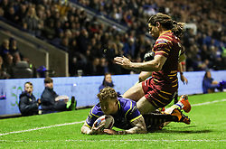 Warrington Wolves' Josh Charnley is tackled by Huddersfield Giants Jake Mamo as he get over the line for a try, during the Betfred Super League match at the Halliwell Jones Stadium, Warrington.