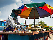 """15 FEBRUARY 2016 - ARANYAPRATHET, SA KAEO, THAILAND:  A Cambodian snack vendor on the Thai side of the border in Aranyaprathet, Thailand. Thais selling bottled water in the border town of Aranyaprathet, opposite Poipet, Cambodia, have reported a surge in sales recently. Cambodian officials told their Thai counterparts that because of the 2016 drought, which is affecting Thailand and Cambodia, there have been spot shortages of drinking water near the Thai-Cambodian and that """"water shortages in Cambodia had prompted people to hoard drinking water from Thailand.""""    PHOTO BY JACK KURTZ"""