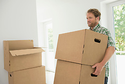 Moving in man carrying boxes new home