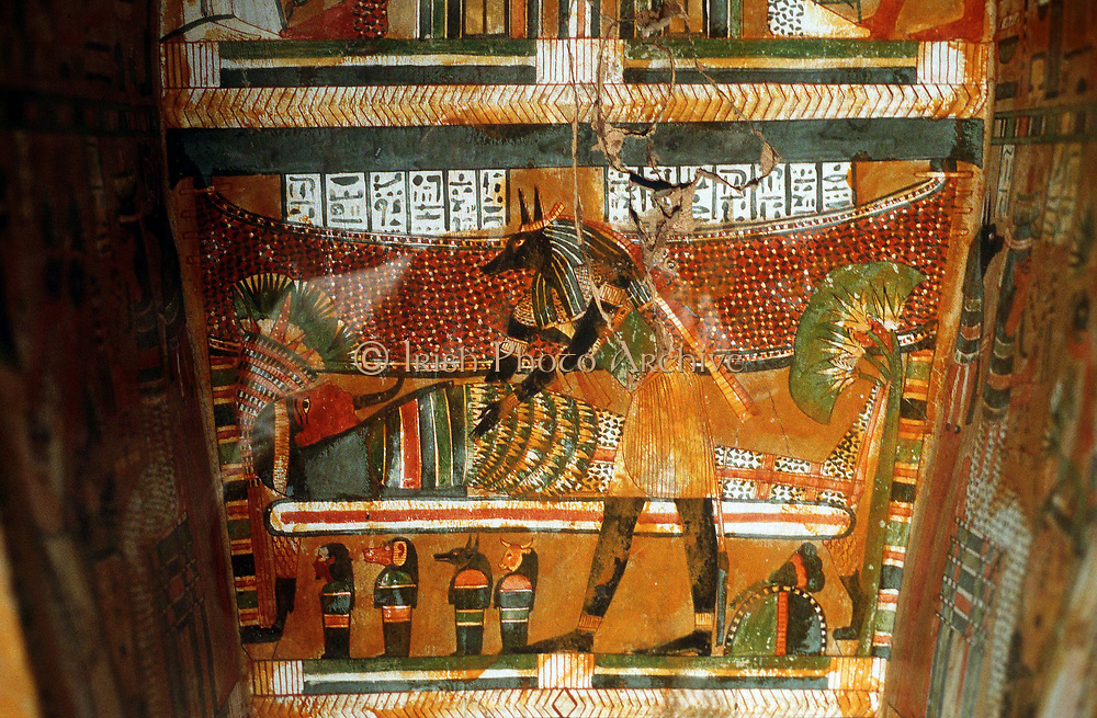 Jackal-headed god Anubis receiving dead king or noble: Painting inside coffin. Anubis, son of Osiris, took souls of dead to his father the judge of the underworld.