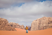 Sudanese Bedouin driver Ahmed stands in the desert in Wadi Rum, Jordan.