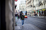 A man wearing a face mask walking in the Prague city center whild doing a phone call. As of 21st of October 2020 people have to wear face masks outside and inside.