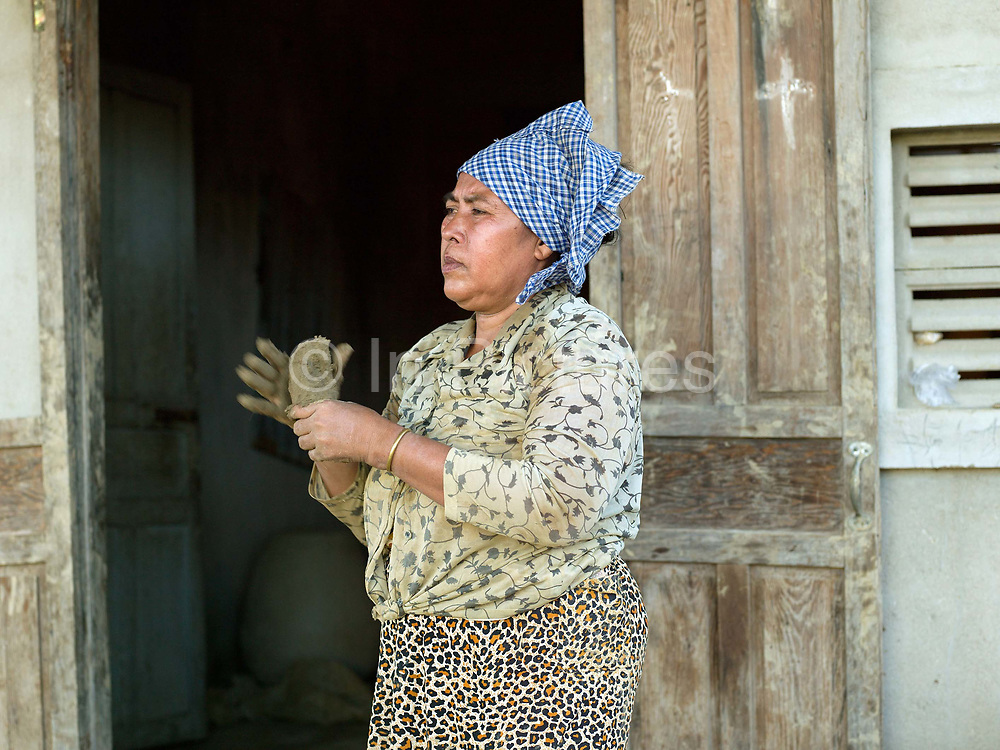 A Hindu Cham woman preparing clay to make a ceramic barbeque using a traditional method in the famous pottery village of Bau Truc in Central Vietnam. Cham potters do not use a wheel to make pots, instead clay is pressed into shape using the hands. Layers of clay are added to the original piece and the potter moves around the object, pressing the clay into the desired shape. They are then put directly in the sun and completely bone dried, making them ready to be fired. Firing is done in an open pit with temperatures going up to 800 degree Celcius. The pots are arranged together and covered with layers of rice straw, which is set on fire.