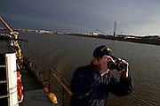 U.S. Coast Guard Seaman  Adam Garloch looks out for another vessel on as they patrol the Potomac River as a part of security measures taken for the Presidential Inauguration ceremonies in Washington, D.C., on January 21, 2013.