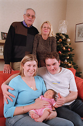 Family group with three generations together in living room,