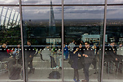 Visitors admire the London skyline from the Sky Garden of the Walkie Talkie building in the City of London. Seen through the outer plate glass window, we see visitors inside enjoying drinks and the panoramic view, reflected in the distance. 20 Fenchurch Street is a commercial skyscraper in London that takes its name from its address on Fenchurch Street, in the historic City of London financial district. It has been nicknamed The Walkie-Talkie because of its distinctive shape. Construction was completed in spring 2014, and the top-floor 'sky garden' was opened in January 2015. The 34-storey building is 160 m (525 ft) tall, making it the fifth-tallest building in the City of London. Designed by architect Rafael Viñoly and costing over £200 million.