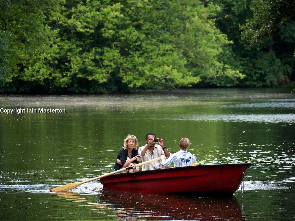 People rowing boats in lake at Tiergarten park in Berlin Germany