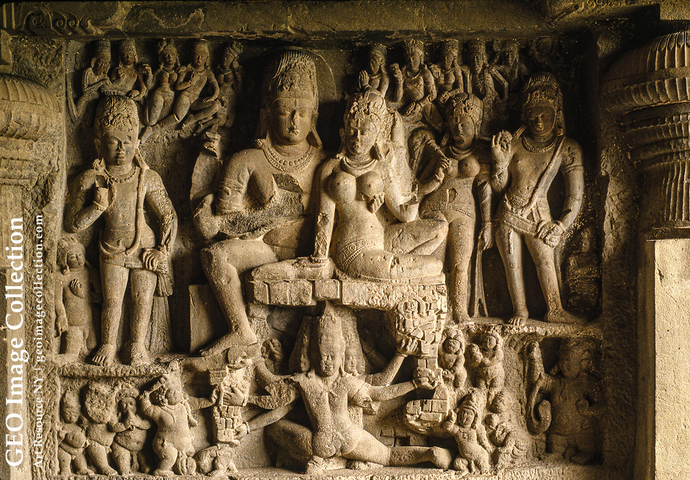 """Legend says that the Hindu gods and nymphs once petitioned Indra, the king of h eaven, for permission to spend a moonlit night on earth. Frolicking on the clif f of Ellora, the deities broke their promise to leave by sunrise -- and turned to stone in the midst of dancing and lovemaking.  Images of Shiva, Vishnu, and their consor ts inhabit some of the world's largest and liveliest sculptures -- the temples carved into the hillside at Ellora in western India, all carved between the six th and twelfth centuries A.D.  The Hindu pantheon shares the mile-long scarp with temp les and deities of Buddhism and Jainism.  Seen here is the marriage of Shiva an d Parvati in Cave No. 29, the Sitaki Nahani. Shiva, the Auspicious One, is one of the most complex gods of India, combining seemingly contradictory qualities: destroyer a nd restorer, great ascetic and symbol of sensuality, benevolent herdsman of sou ls and wrathful avenger.  His consort Parvati, the benevolent aspect of the god dess Sakti, is always represented as a mature and beautiful woman.  The figure beneath the nuptial pair is Ravana, the ten-headed demon-king of Lanka (Ceylon), who in the """"Ramayana"""" abducted Sita, wife of Rama, and took her to Ceylon.  Among his man y misdeeds, Ravana shook Sh iva's sacred mountain, Kailasa, to show he was as powerful as t he deity; but Shiva stopped him by pressing the mountain down with his toe and kept him imprisoned beneath for 1,000 years, as apparently shown here.  This ca rving was done c. 580-642."""