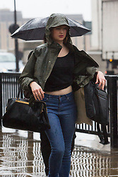 © Licensed to London News Pictures. 13/10/2014. London, UK. Commuters walk to work over London Bridge during heavy rain in the City of London this morning, 13th October 2014. Photo credit : Vickie Flores/LNP
