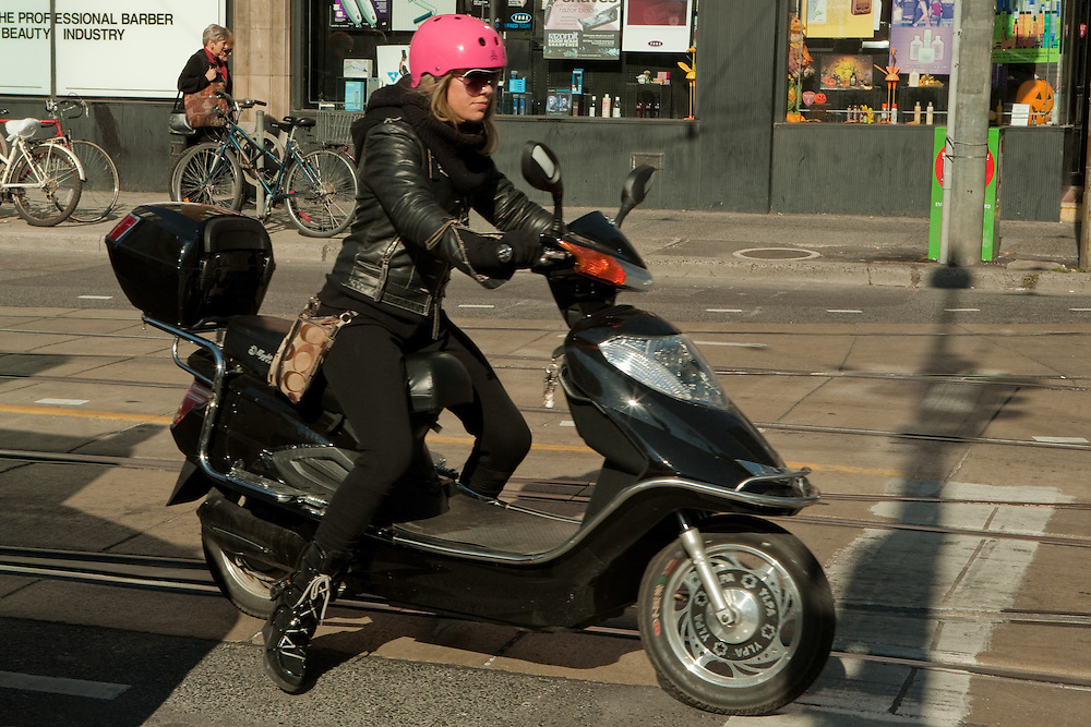 A young woman wearing a pink motorcycle helmet riding a motor scooter on Toronto's Dundas Street West.