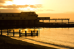 © Licensed to London News Pictures. 31/12/2016. Aberystwyth, Wales, UK. Sunset over the seaside pier  in Aberystwyth on the last day of the year - - the weather in the west has been clear, in sharp contrast to the thick fog covering much of south east England. Photo credit: Keith Morris/LNP