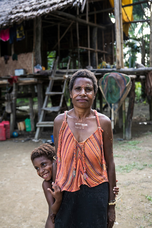 Lucy, standing with granddaughter Carisa, age 7, in Yar village, East Sepik Province, Papua New Guinea<br /> <br /> (June 21, 2019)