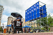 Wilkes-Barre, PA (July 11, 2020) -- A woman uses an umbrella for shade at the Black Lives Matter NEPA United Movement event on Public Square.