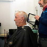 Barber Paul Youle and a customer at his barber's shop 'Stallions', Parson Cross, Sheffield, South Yorkshire, UK