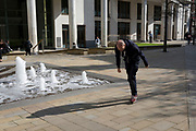 A man recovers and straightens after checking his shoelaces in the City of London, the capital's financial district, on 1st April, 2019, in London England.