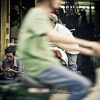 scooter passes by man working on sidewalk, Saigon, Vietnam