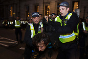 Metropolitan Police officers detain a man who had been attending a National Demonstration for a Free Education on 4th November 2015 in London, United Kingdom. The demonstration was organised by the National Campaign Against Fees and Cuts NCAFC in protest against tuition fees and the Government's plans to axe maintenance grants with effect from 2016.