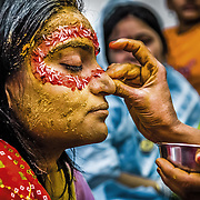 An ellaborate design is created on the face of a Rajput bride during her Haldi ceremony. Gwalior, 2007