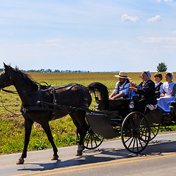 Strasburg, PA – June 19, 2016: An Old Order Amish family ride in an open wagon in Lancaster County, Pennsylvania.