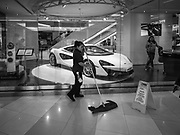 17 DECEMBER 2018 - BANGKOK, THAILAND: A mall employee cleans the floor in front of the McClaren showroom in Siam Paragon, an exclusive mall in central Bangkok. According to Credit Suisse Global Wealth Databook 2018, which surveyed 40 countries, Thailand has the highest rate of income inequality in the world. In 2016, Thailand was third, behind Russia and India. In 2016, the 1% richest Thais (about 500,000 people) owned 58.0% of the Thailand's wealth. In 2018, they controlled 66.9%. In Russia, those numbers went from 78% in 2016, down to 57.1% in 2018. The Thai government disagreed with the report and said the report didn't take government anti-poverty programs into account and that Thailand was held to an unfair standard because most of the other countries in the report are developed countries in the Organisation for Economic Co-operation and Development.    PHOTO BY JACK KURTZ