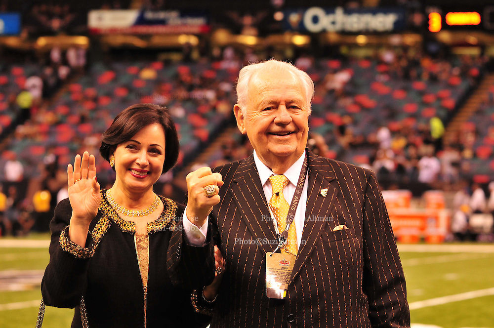 "World Champion New Orleans Saints owner Tom Benson shows off his Super Bowl Ring and his one of a kind hand made ""special ""pinstripe suit"" The striping says "" New Orleans Saint World Champions"" all over the  Black & Gold Suit!!! His wife Gayle , on his arm,had it made for him as a surpirse and he was presented it right before opening of the NFL season in New Orleans Louisiana Thurs Sept. 9,2010. The Saints beat the Minnessota Viking 14-9. Phot © Suzi Altman"
