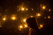 """4th December 2014, New Delhi, India. A woman passes in front of a wall lit by candles left by believers who come to pray, make offerings and ask for wishes to be granted by Djinns in the ruins of Feroz Shah Kotla in New Delhi, India on the 4th December 2014<br /> <br /> PHOTOGRAPH BY AND COPYRIGHT OF SIMON DE TREY-WHITE a photographer in delhi<br /> + 91 98103 99809. Email: simon@simondetreywhite.com<br /> <br /> People have been coming to Firoz Shah Kotla to leave written notes and offerings for Djinns in the hopes of getting wishes granted since the late 1970's. Jinn, jann or djinn are supernatural creatures in Islamic mythology as well as pre-Islamic Arabian mythology. They are mentioned frequently in the Quran  and other Islamic texts and inhabit an unseen world called Djinnestan. In Islamic theology jinn are said to be creatures with free will, made from smokeless fire by Allah as humans were made of clay, among other things. According to the Quran, jinn have free will, and Iblis abused this freedom in front of Allah by refusing to bow to Adam when Allah ordered angels and jinn to do so. For disobeying Allah, Iblis was expelled from Paradise and called """"Shaytan"""" (Satan).They are usually invisible to humans, but humans do appear clearly to jinn, as they can possess them. Like humans, jinn will also be judged on the Day of Judgment and will be sent to Paradise or Hell according to their deeds. Feroz Shah Tughlaq (r. 1351–88), the Sultan of Delhi, established the fortified city of Ferozabad in 1354, as the new capital of the Delhi Sultanate, and included in it the site of the present Feroz Shah Kotla. Kotla literally means fortress or citadel. 4th December 2014, New Delhi, India. A woman stands by a wall covered with candles as offerings to Djinns in the ruins of Feroz Shah Kotla in New Delhi, India on the 4th December 2014<br /> <br /> PHOTOGRAPH BY AND COPYRIGHT OF SIMON DE TREY-WHITE a photographer in delhi<br /> + 91 98103 99809. Email: simon@simondetreywhite."""