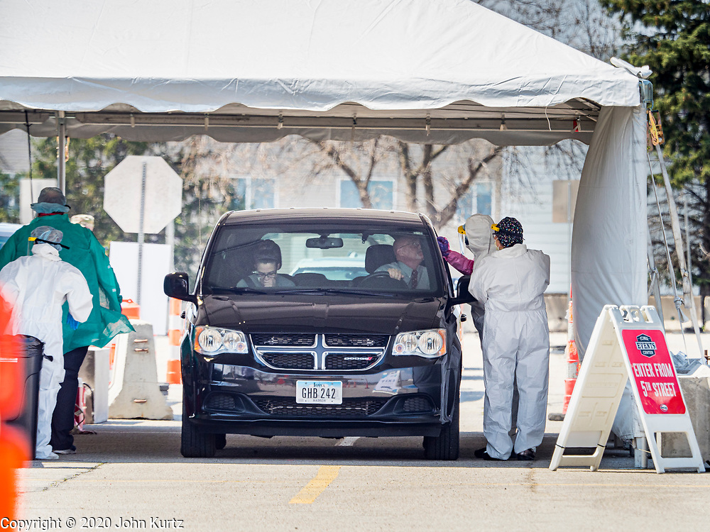 """26 APRIL 2020 - DES MOINES, IOWA: Medical workers conduct tests for COVID-19 at the first drive through testing site in Iowa. Iowa started mass testing Saturday, with a drive through testing site in a parking lot in downtown Des Moines. The testing this weekend is considered a """"soft opening"""" for the program and tests were reserved for medical professionals and first responders. Despite numerous outbreaks in meat packing plants throughout Iowa, members of the public have not been able to get tested. On Saturday, 25 April, there were 5,092 confirmed cases of COVID-19 (Coronavirus / SARS-CoV-2) in Iowa (an increase of 647 since Friday, April 24) and 112 deaths in Iowa caused by COVID-19.          PHOTO BY JACK KURTZ"""
