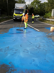 © Licensed to London News Pictures. 17/09/2021. Leatherhead, UK. Highways England workers attempt to clean blue paint from the road surface on the slip road of junction 9 of the M25 in Leatherhead after climate change protesters stopped traffic. Police have cleared a group of protesters who were blocking the roundabout at the exit of the M25 at junction 9 Leatherhead in Surrey. Photo credit: Peter Macdiarmid/LNP