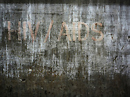 old awareness raising sign about HIV / AIDS is fading on a wall.