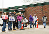 Supporters with signs stand outside the Gilmanton Elementary School on Tuesday afternoon  as a steady stream of voters pass by.  (Karen Bobotas/for the Laconia Daily Sun)