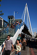 Tourists cross Golden Jubilee Bridges, the foot bridge which crosses Hungerford Bridge, Westminter, London.