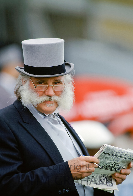 Racegoer, with traditional handlebar moustache, checking racing form front of the Grandstand at Epsom Racecourse on Derby Day, UK