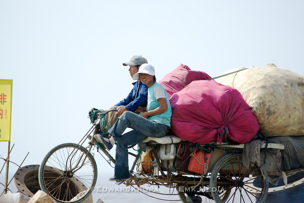 A couple riding on a motorized tricycle by the South China Sea near Wenzhou.