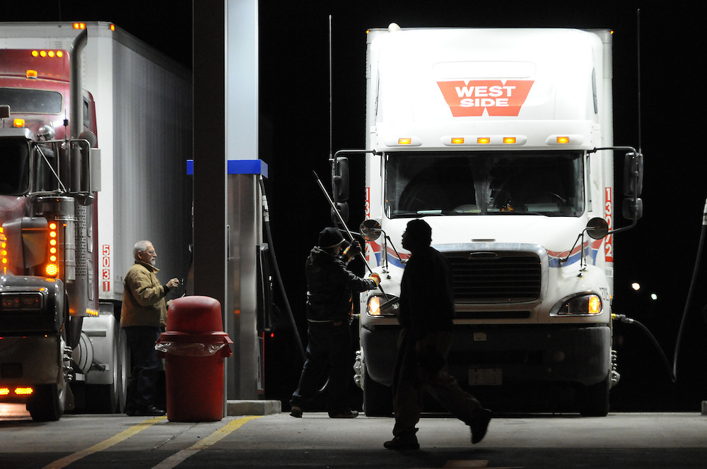 Trucker David Strese clears the headlights on his rig while he and William Miller (L) fill up at the new refueling island at the TA Travel Centers of America in Morris, Illinois.