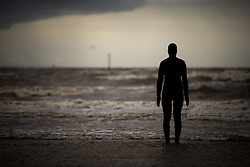 "© Licensed to London News Pictures . Crosby , UK . File picture dated 07/07/2015 of Crosby Beach , featuring an "" iron man "" , a part of Antony Gormley's "" Another Place "" installation . The organisation that brought the installation to the site , Regenerus (or South Sefton Development Trust as it was in Summer 2005) is celebrating the tenth anniversary since its installation , at an exhibition starting today (7th September 2015) at nearby Crosby Lakeside Adventure Centre . Photo credit : Joel Goodman/LNP"