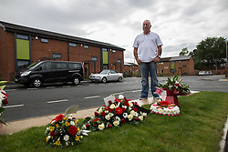 "© Licensed to London News Pictures . 28/08/2015 . Salford , UK . Paul Massey's brother JOHN MASSEY looks at flowers and tributes , left on Sedan Close in Salford , from where the procession sets off . The funeral of Paul Massey at St Paul's CE Church in Salford . Massey , known as Salford's "" Mr Big "" , was shot dead at his home in Salford last month . Photo credit : Joel Goodman/LNP"