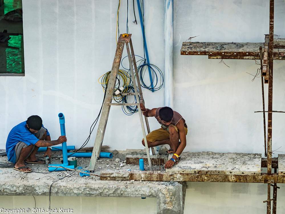 """23 AUGUST 2016 - NONTHABURI, NONTHABURI, THAILAND: Construction workers work on buildings near the """"Purple Line,"""" the new Bangkok commuter rail line that runs from Bang Sue, in Bangkok, to Nonthaburi, a large Bangkok suburb. The Purple Line is run by the  Metropolitan Rapid Transit (MRT) which operates Bangkok's subway system. The Purple Line is the fifth light rail mass transit line in Bangkok and is 23 kilometers long. The Purple Line opened on August 6 and so far ridership is below expectations. Only about 20,000 people a day are using the line; officials had estimated as many 70,000 people per day would use the line. The Purple Line was supposed to connect to the MRT's Blue Line, which goes into central Bangkok, but the line was opened before the connection was completed so commuters have to take a shuttle bus or taxi to the Blue Line station. The Thai government has ordered transit officials to come up with plans to increase ridership. Officials are looking at lowering fares and / or improving the connections between the two light rail lines.     PHOTO BY JACK KURTZ"""