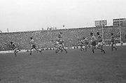 Dublin kicks the ball as Kerry players jump in an attempt to block it during the All Ireland Senior Gaelic Football Final, Kerry v Dublin in Croke Park on the 28th September 1975. Kerry 2-12 Dublin 0-11.