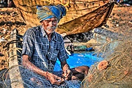 old fisherman is reparing a fishingnet