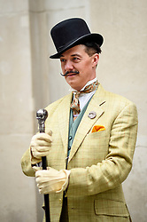 © Licensed to London News Pictures. 14/07/2019. LONDON, UK.  London, UK. 14 July 2019.   An elegantly dressed man takes part in The Grand Flâneur walk.  Starting at the Beau Brummell statue on Jermyn Street, the walk coincides with the 20th anniversary of The Chap magazine and is defined as a walk without purpose, celebrating the art of the flâneur, oblivious to going anywhere specific, and an antidote to the demands of modern life and the digital smartphone.  Similar walks are taking place in Dusseldorf and Los Angeles.  Photo credit: Stephen Chung/LNP