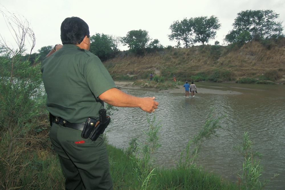 Hispanic male US Border Patrol agent searching Rio Grande, the US/Mexico border, for illegal aliens near Brownsville, Texas.<br /> ©Bob Daemmrich