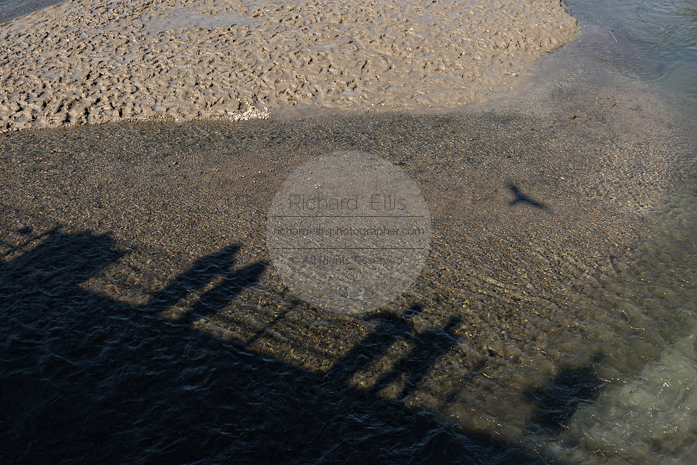 Tourists cast shadows on the mudflats of Ship Creek as they watch fishermen catching salmon from the pedestrian bridge in downtown Anchorage, Alaska.